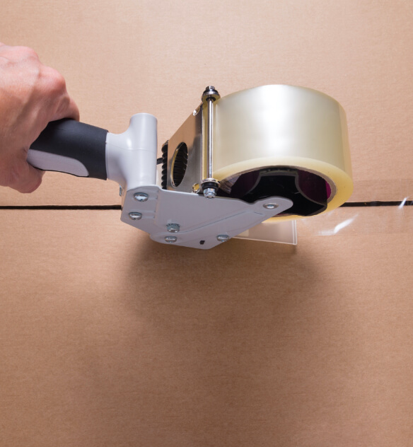 A clear roll of packaging tape being applied to the seam of a cardboard box