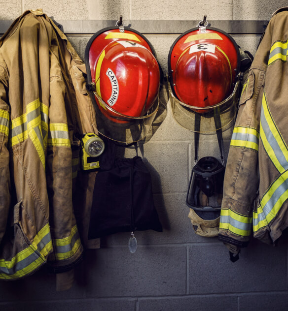 Firefighting jackets, helmets, and masks hanging from hooks on a cement wall