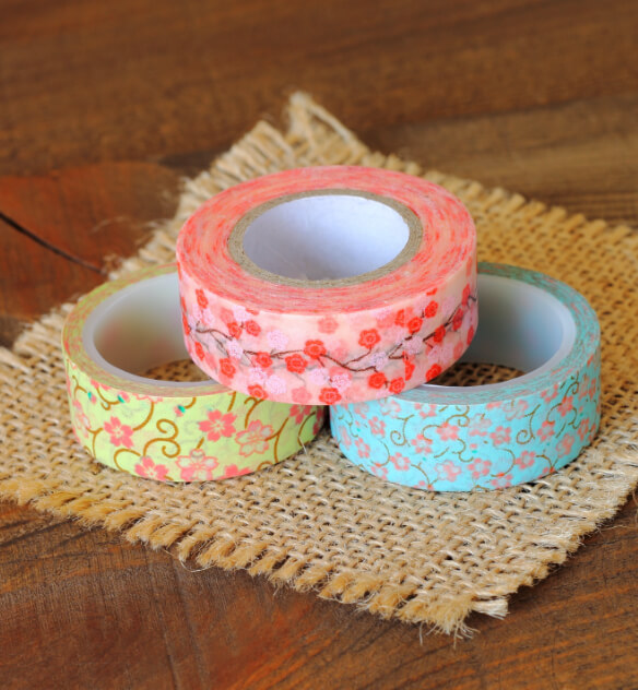 3 rolls of decorative tape designed with pink flower graphics laying on a wooden table