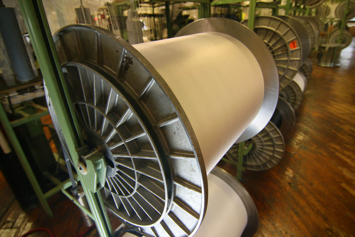 Close up of a large roll of white fabric being stored inside a textile mill