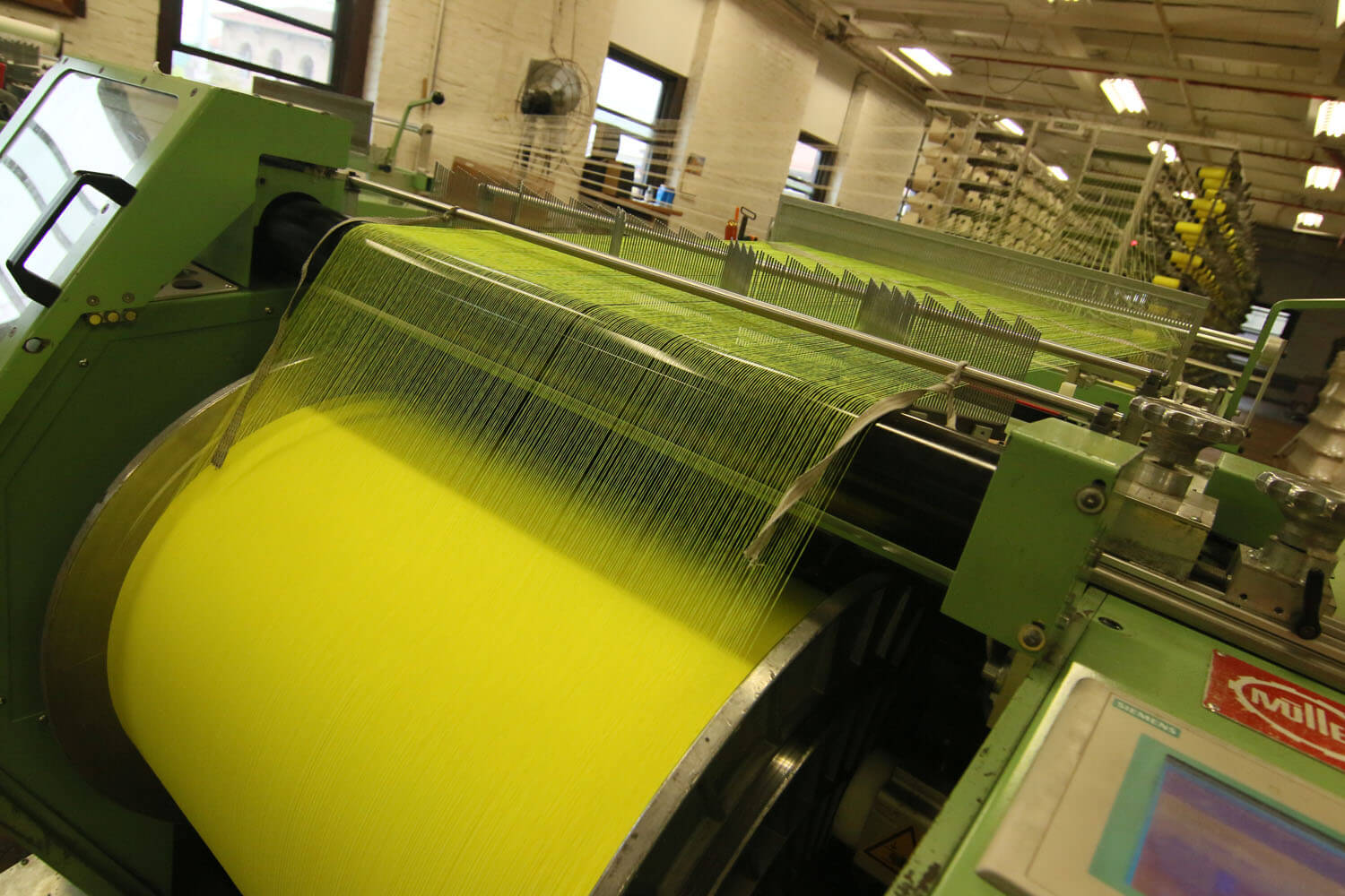 Yellow fabric being rolled into a large spool during the textile manufacturing process