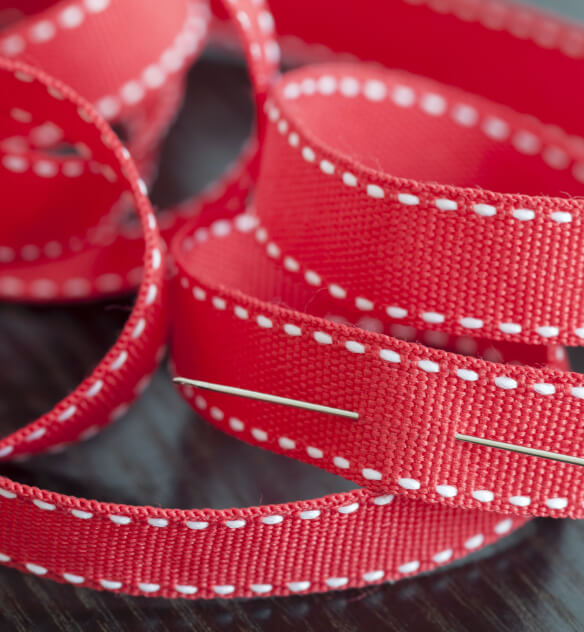 Close up of a piece of red webbing that features 2 dotted white lines and is pierced by a clothing pin