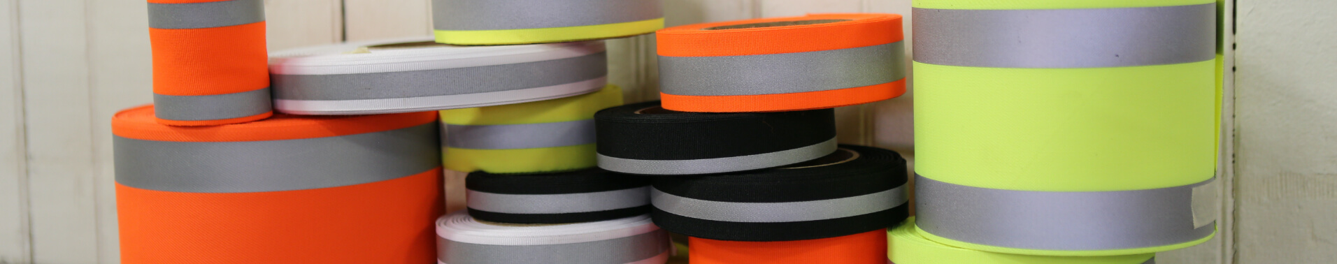 Spools of multi-colored reflective laminated fabric stacked on top of each other