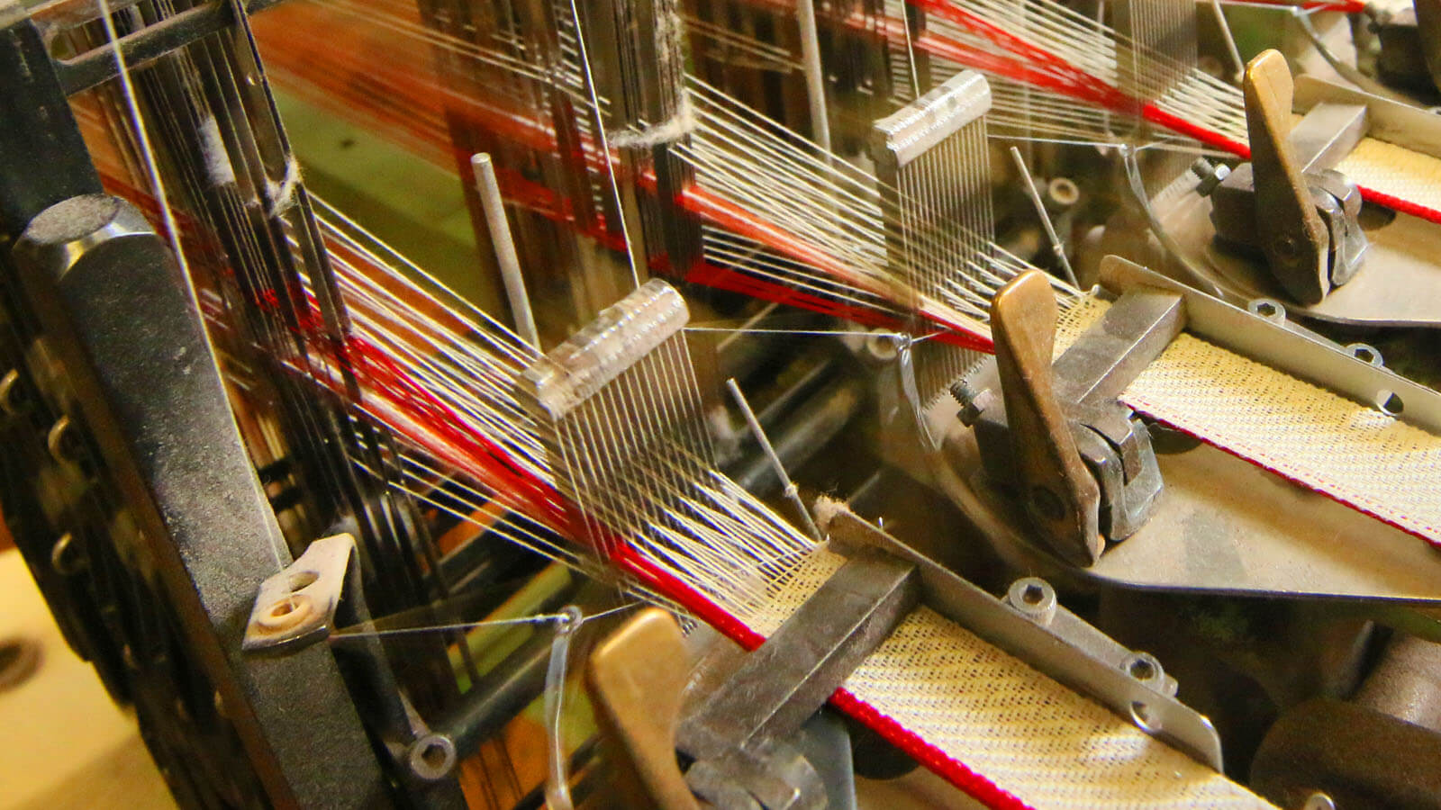 Close-up of fabric being woven by an industrial machine in a factory