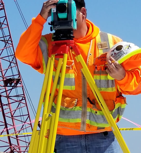 A man in construction gear using a line of sight system outside