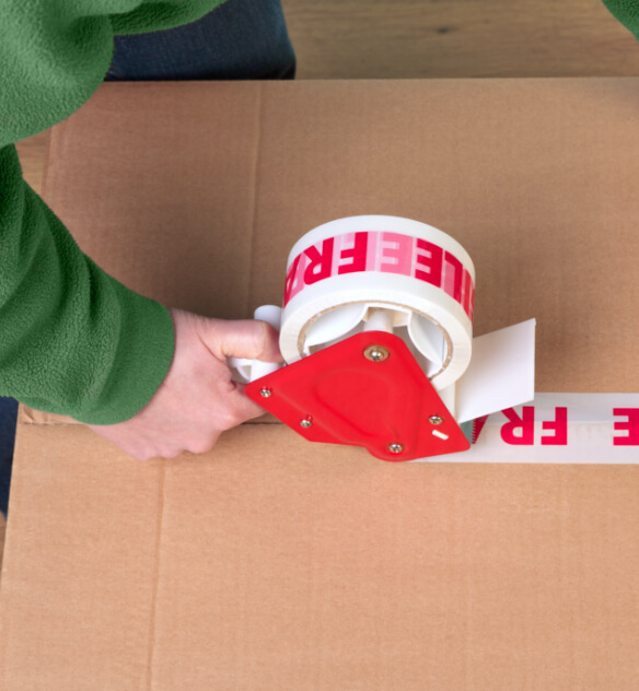 A white roll of packaging tape with the red word FRAGILE printed on it being applied to a cardboard box