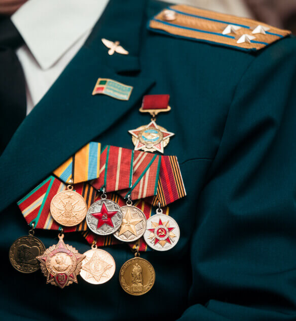 The upper left chest of a dark green military jacket covered by many military award pins.