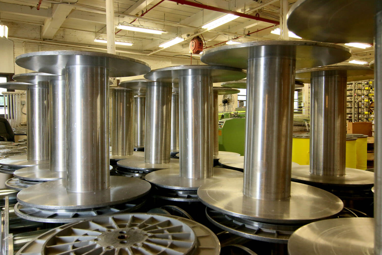 Several large silver empty fabric roll holders inside of a textile facility