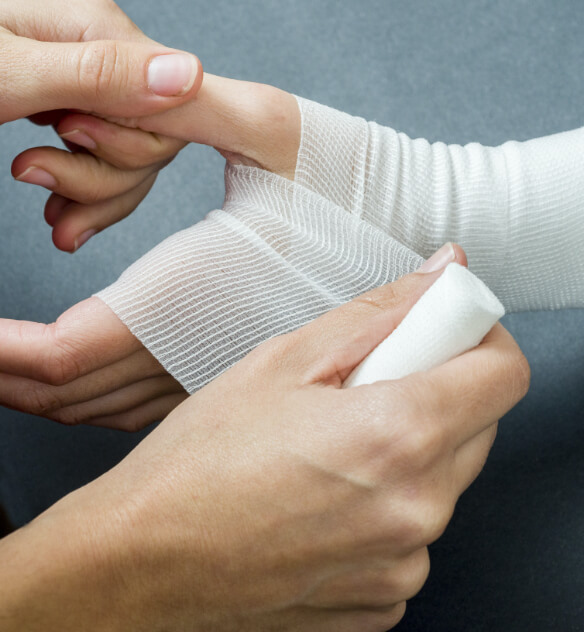 Medical gauze being wrapped around a persons hand