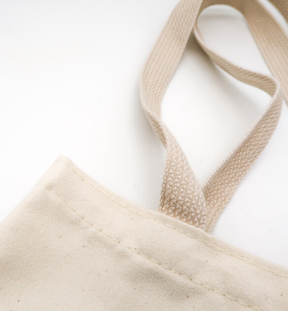 Magnified view of the corner of a tan bag and its handle laying on a white surface