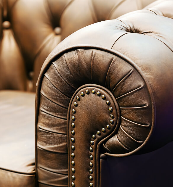 Close up of the arm of a brown leather couch