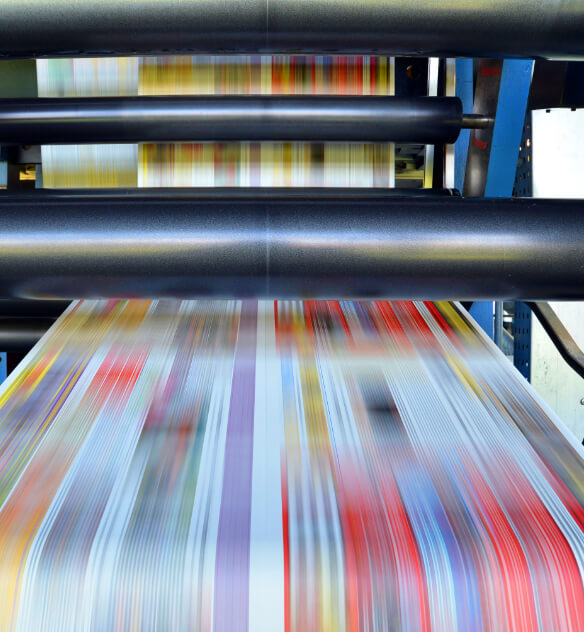 A multicolored sheet of print fabric being quickly processed by a printing press