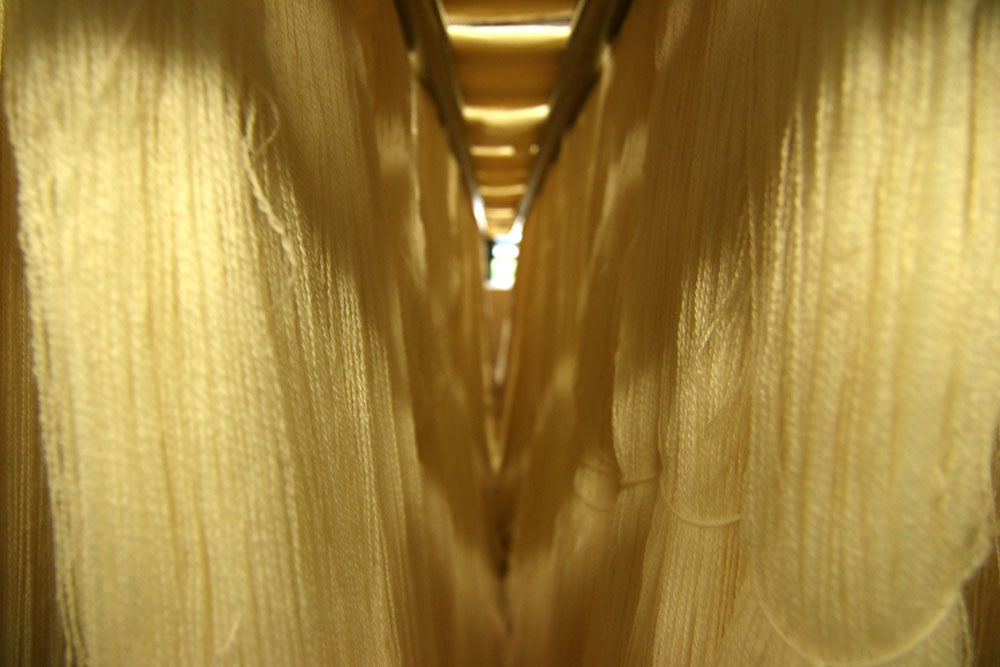Bunches of white string fabric hanging in storage inside a textile facility