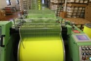 Strands of yellow fabric being rolled together at the end of the textile manufacturing process