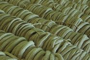 Dozens of dark green drawstrings being processed in a textile facility