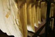 Thick sections of tan fabric being hung together in a textile mill
