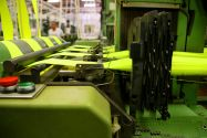 A machine in a textile mill manufacturing large pieces of yellow fabric with an employee in the background