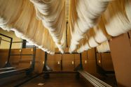 Sections of white fabric hanging on a storage rack inside a textile mill