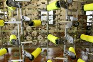 Several small rolls of yellow and white fabric being processed by a tall metal piece of machinery