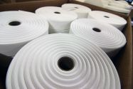 Close up of several rolls of white fabric sitting in a cardboard box