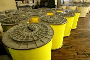 Dozens of large rolls of yellow and tan fabric sitting inside of a textile facility
