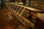 A large wooden piece of textile machinery manufacturing white fabric