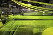 Textile machinery processing strands of yellow fabric