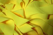 Long pieces of bright yellow fabric tangled together